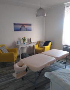 photo du cabinet avec la table de massage et deux fauteuils jaunes